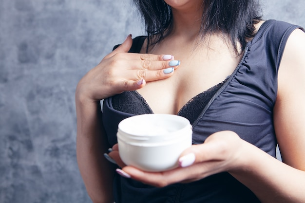 若い女性が灰色の背景にクリームで胸を塗りつける