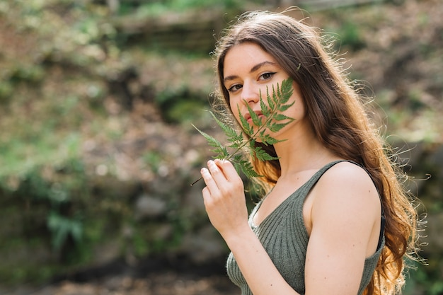 Young woman smelling on a leaf in forest