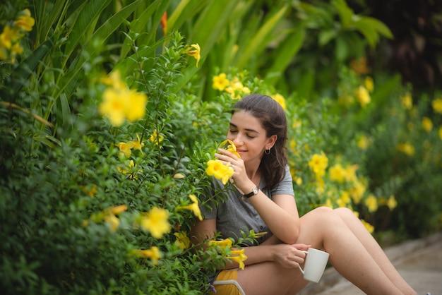 黄色の花の臭いがする若い女性