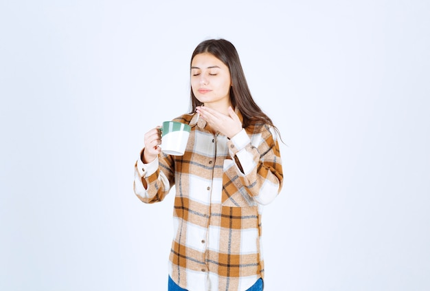 Young woman smells aroma of cup of coffee over white wall.