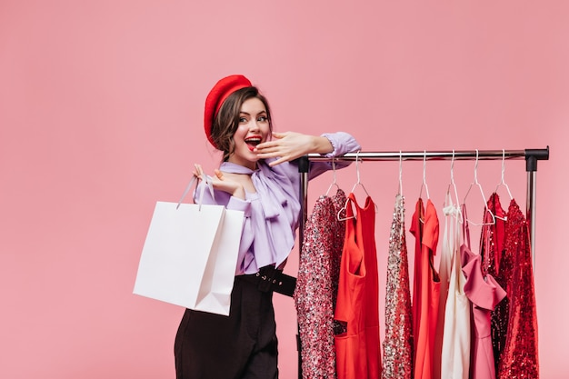 Young woman smiles and covers her mouth while shopping. lady in beret poses near stand with fancy dresses.