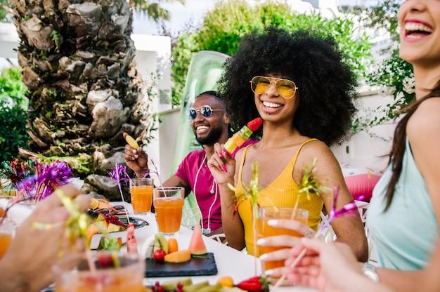 Молодая женщина улыбается и празднует с друзьями