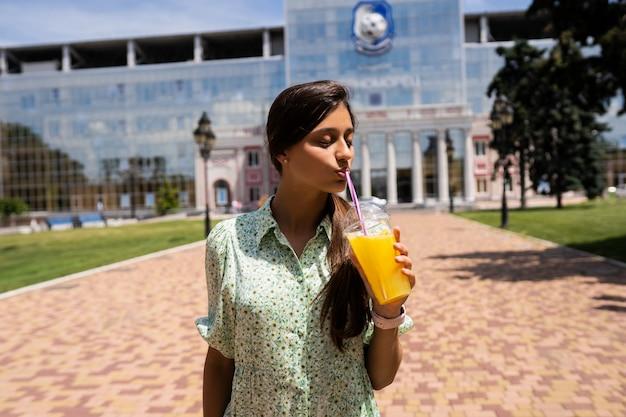 若い女性が笑顔で街の通りにストローとプラスチックカップで氷とカクテルを飲みます。