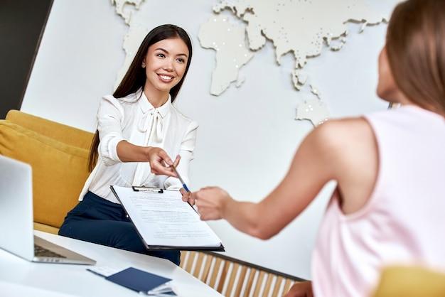 Молодая женщина улыбается и дает контракт туристу