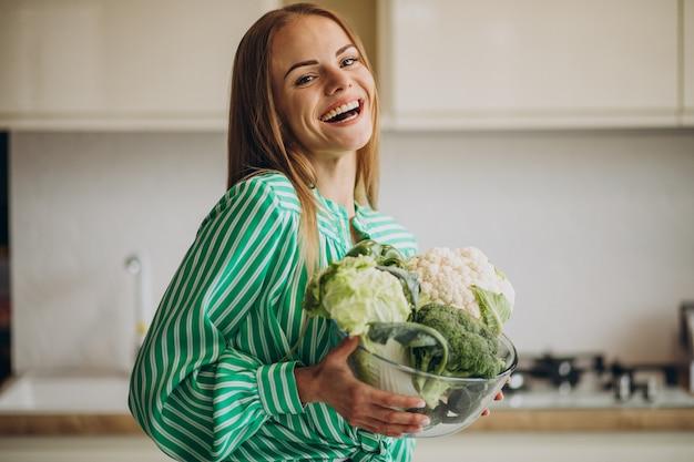 Молодая женщина улыбается и держит цветную капусту