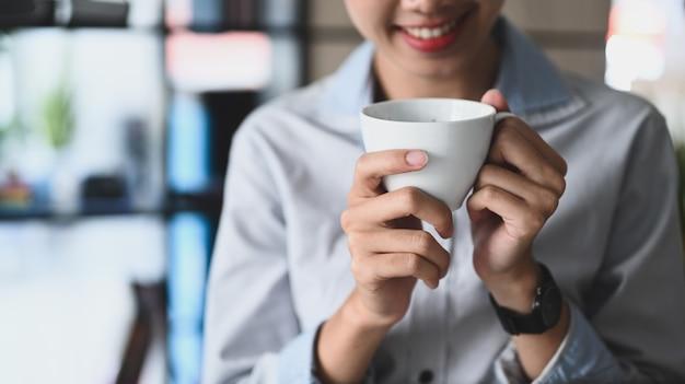 Молодая женщина улыбается и держит чашку горячего напитка.