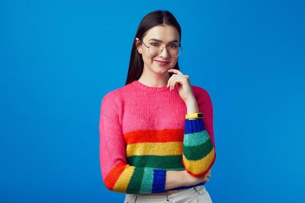 Молодая женщина улыбается и держится за руки, частично скрещенные, носит радужный свитер