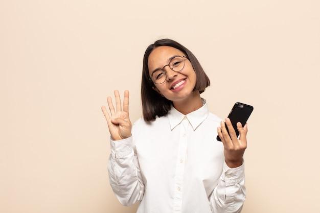 젊은 여자가 웃고 친절하게보고, 앞으로 손으로 4 번 또는 4 번을 보여주는