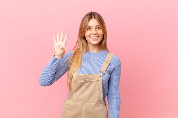 Молодая женщина улыбается и выглядит дружелюбно, показывая номер четыре