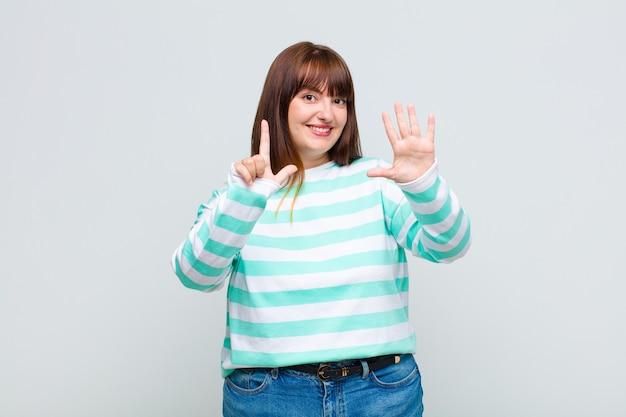 젊은 여자가 미소하고 친절하게보고, 앞으로 손으로 일곱 번째 또는 일곱 번째를 보여주는, 카운트 다운