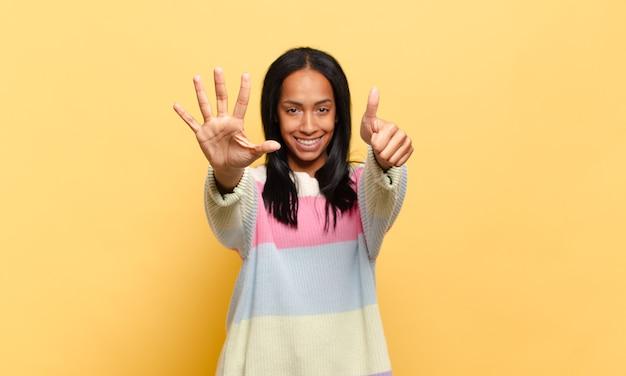 笑顔でフレンドリーに見える若い女性、前に手を前に6番または6番を示し、カウントダウン