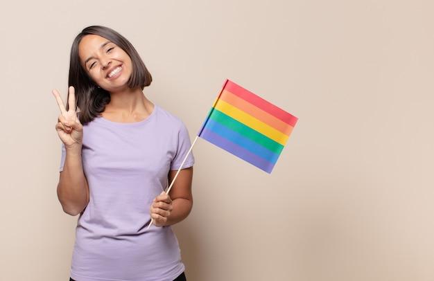 Молодая женщина улыбается и выглядит дружелюбно, показывает номер два или секунду рукой вперед, отсчитывая
