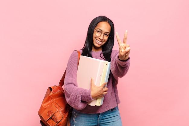 笑顔でフレンドリーに見える若い女性、前に手を前に2番目または2番目を示し、カウントダウン