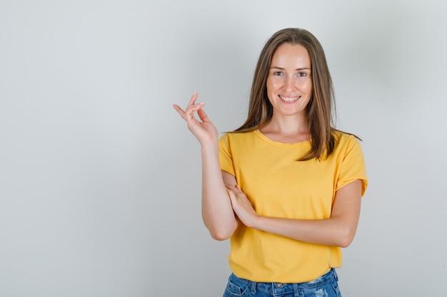 Молодая женщина улыбается и указывает в футболке