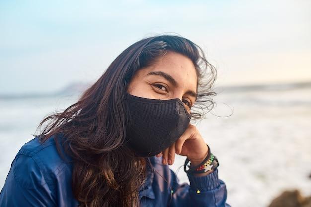 笑顔で桟橋にフェイスマスクを身に着けている若い女性。日没時のアウトドアスポーツ。日没で休んでいる無料の女性