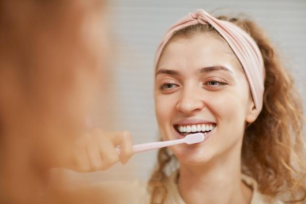 아침에 그녀의 이빨을 청소하는 동안 앞에 웃는 젊은 여자