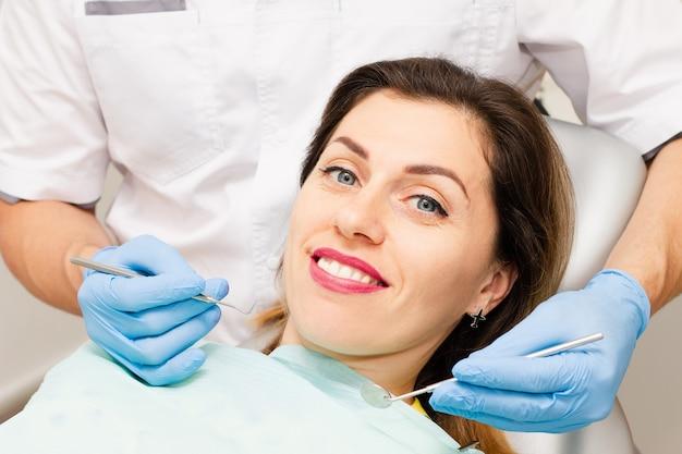 Молодая женщина улыбается на приеме у дантиста.