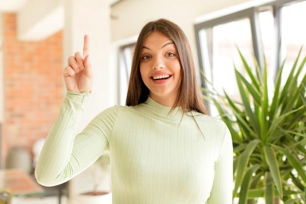 スペースをコピーするために片手で元気にそして幸せに上向きに笑っている若い女性