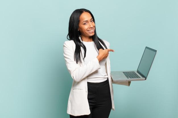 젊은 여성은 즐겁게 웃고 행복하며 옆과 위쪽을 가리키며 복사 공간에 물건을 보여줍니다.