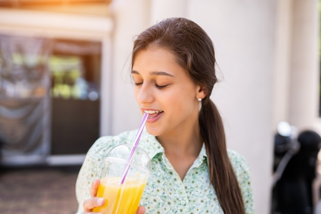 Young woman smiling and drinking cocktail with ice in plastic cup with straw on city street.