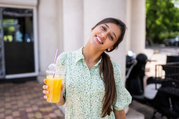Young woman smiling and drinking cocktail with ice in plastic cup with straw
