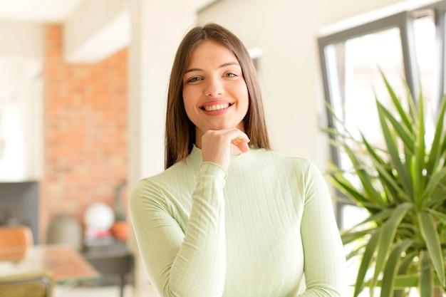 あごに手を当てて幸せでフレンドリーな満足と屈託のない人生を楽しんで笑っている若い女性