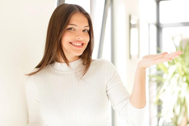 자신감이 성공하고 측면에 뭔가 보여주는 행복을 느끼고 웃는 젊은 여자