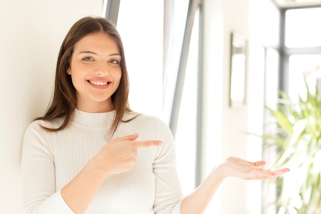 Young woman smiling feeling happy carefree and satisfied pointing to concept or idea on copy space on the side
