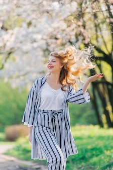 Young woman smiling in the flowered garden in the springtime. girl under blossom tree. summer fashion concept. Premium Photo