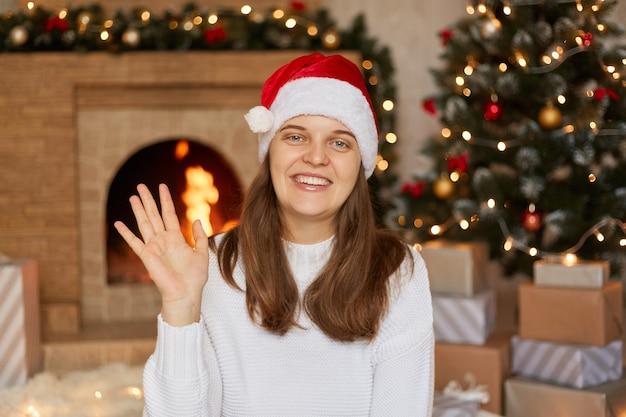 若い女性は幸せにそして元気に笑って、手を振って、誰かを歓迎して挨拶するか、さようならを言って、サンタの帽子とセーターを着て、クリスマスツリー、暖炉と贈り物の箱の近くでポーズをとる。