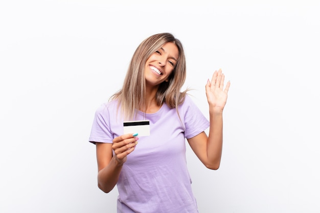 Young woman smiling happily and cheerfully, waving hand, welcoming and greeting you, or saying goodbye with a credit card