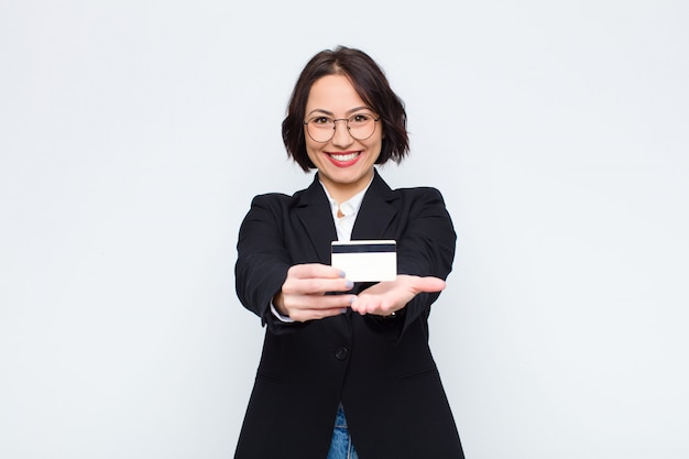 Young woman smiling happily with friendly, confident, positive look, offering and showing an object or concept with a credit card
