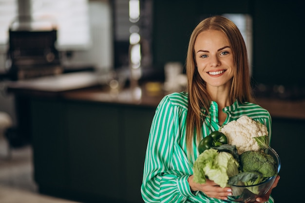 Young woman smiling and holding cauliflower