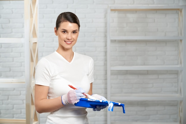 Young woman smiling and holding paint in empty room
