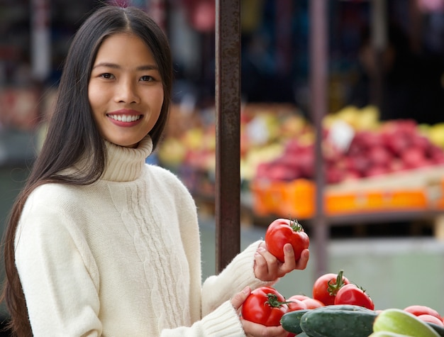 Young woman smiling and holding vegetables at market