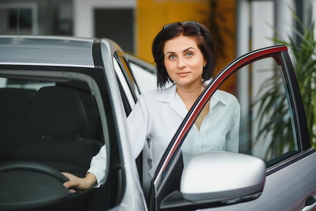 Молодая женщина улыбается в своей новой машине в автосалоне