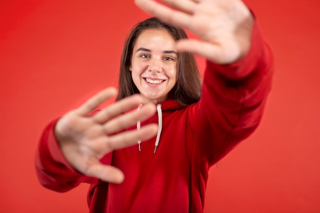 Молодая женщина улыбается изолированной на красном