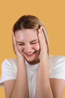 노란색에 고립 된 웃는 젊은 여자