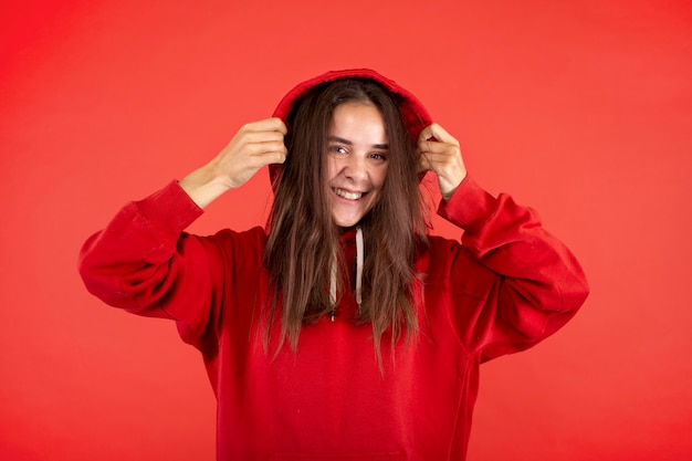 Young woman smiling isolated on red