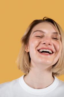 Giovane donna sorridente isolata su yellow