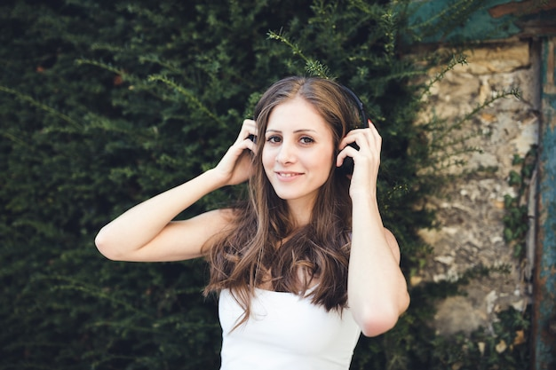 Young woman smiling and listening to music via headphones outdoors