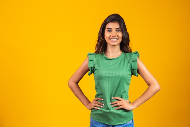 Young woman smiling looking at camera on yellow background.