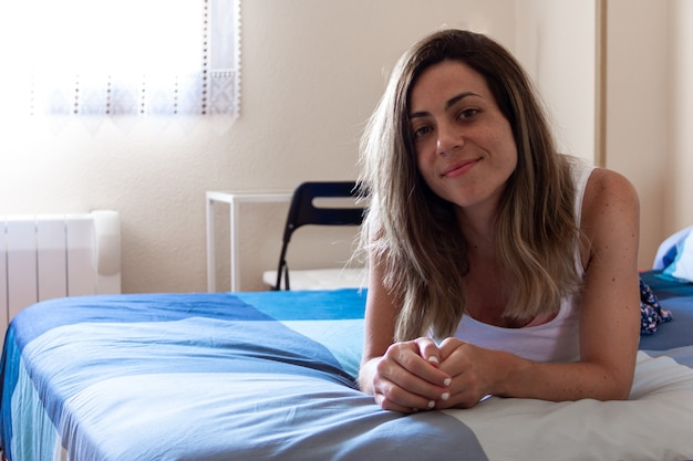 Young woman smiling lying on the bed in the room. selective focus. copy space.