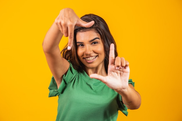 Молодая женщина улыбается, делая фоторамку руками и пальцами с счастливым лицом. концепция творчества и фотографии.