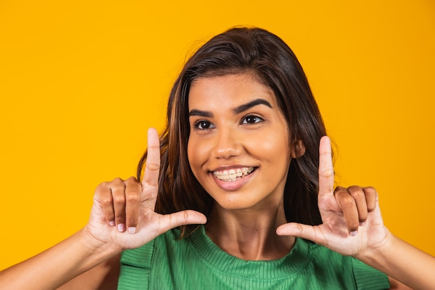 Young woman smiling making photo frame with hands and fingers with a happy face. creativity and photography concept.
