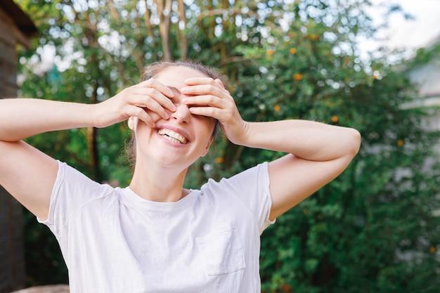 야외 웃는 젊은 여자. 공원이나 정원 녹색 배경에서 쉬고 있는 아름다운 브루넷 소녀. 여름에 무료 행복한 여자. 자유 행복 평온한 행복한 사람들 개념입니다.