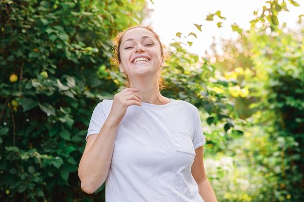 야외 웃는 젊은 여자. 공원이나 정원의 녹색 장면에서 쉬고 있는 아름다운 갈색 머리 소녀