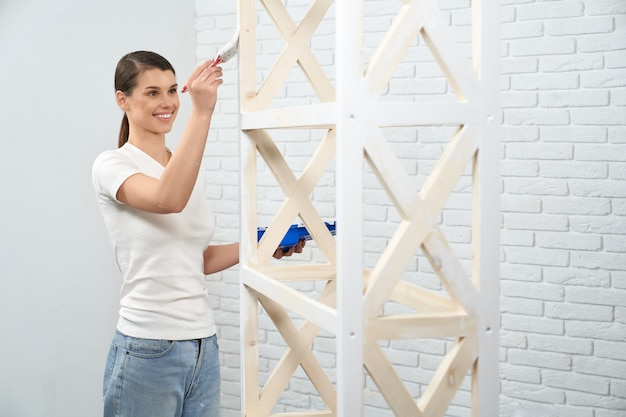 Young woman smiling and painting wooden rack