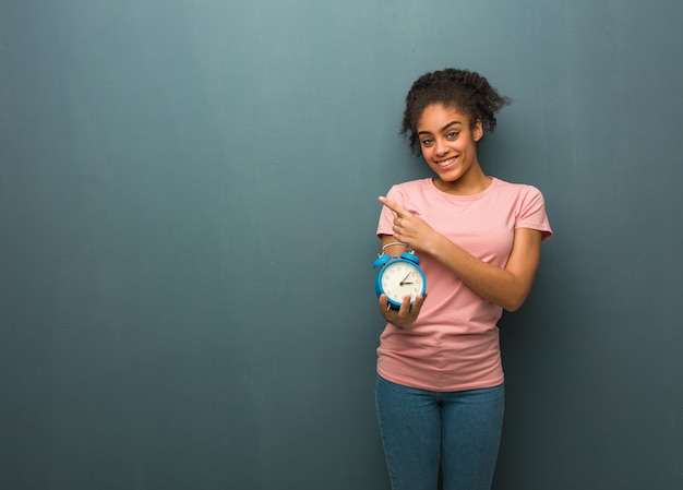 Young woman smiling and pointing to the side she is holding an alarm clock.