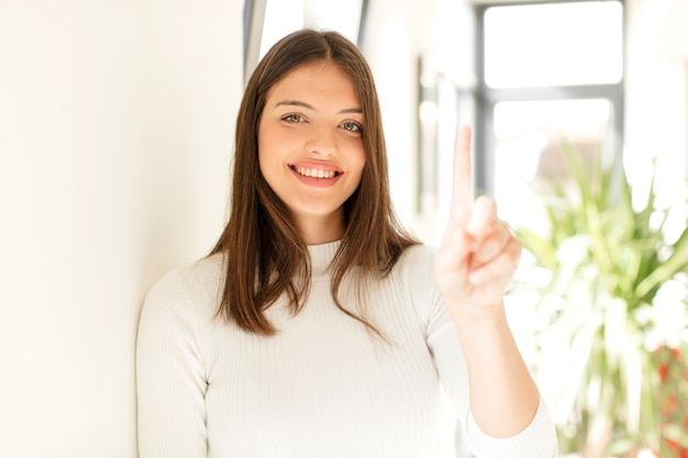 Young woman smiling proudly and confidently making number one pose triumphantly feeling like a leader